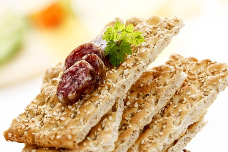 Staplad sesamknäckebröd med skivor av salami arkivbild
