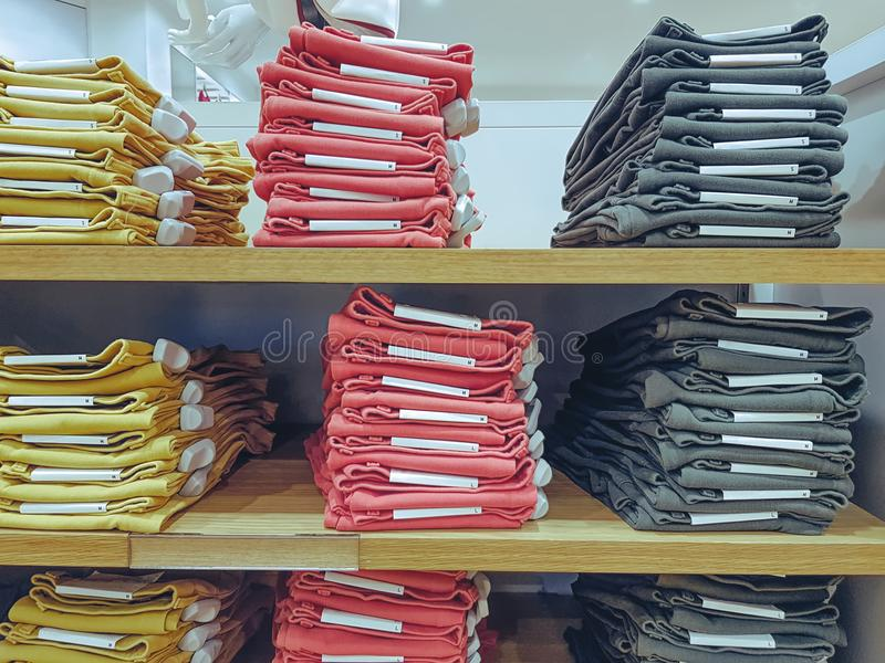Staplad vikt färgrik jeans på hylla på klädlagret arkivbilder