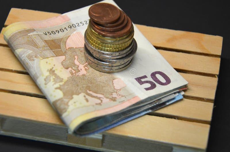 Staplade eurosedlar och myntpengar på paletten besparingar arkivfoto