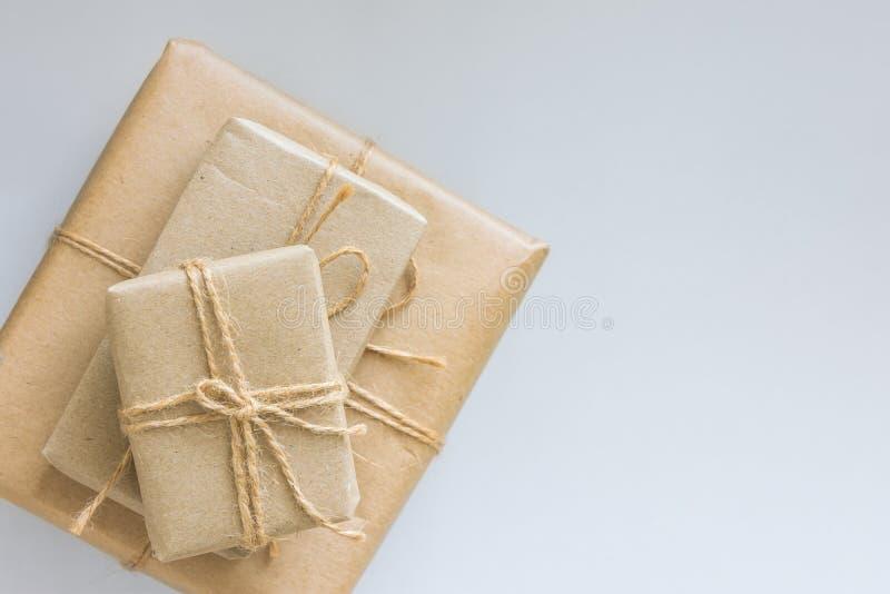 Staplade gåvaaskar som slås in i brunt hantverkpapper som binds med, tvinnar olika format Bästa sikt för vit bakgrund Nya år för  fotografering för bildbyråer