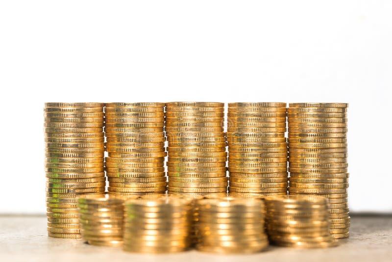 Staplade guld- mynt på vit bakgrund royaltyfri bild