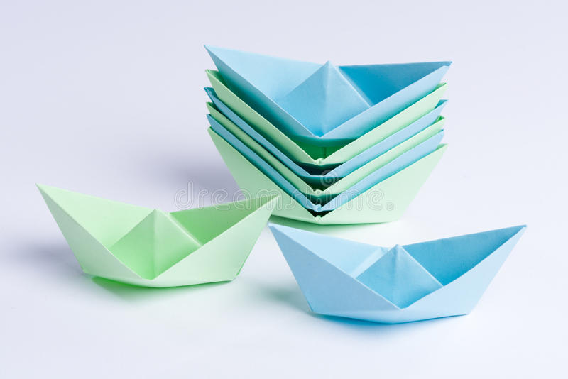 Staple of blue and green origami paper ships stock photo