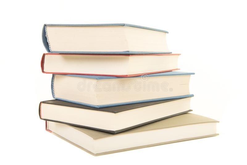 Staple of five books seen from the front. Isolated on a white background royalty free stock photos