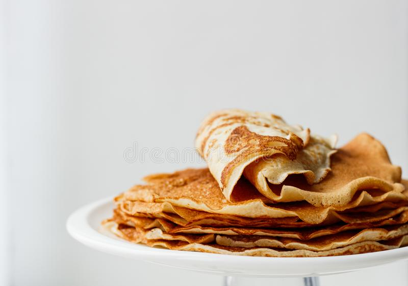 Staple of wheat golden yeast pancakes or crepes in a white plate closeup  on a white background royalty free stock images