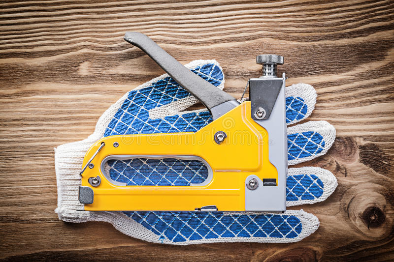 Stapler gun pair of working gloves on wooden board construction. Concept royalty free stock photo