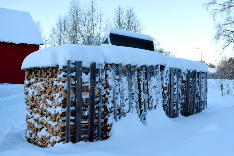 Staplungsbrennholz auf dem Schnee lizenzfreies stockfoto