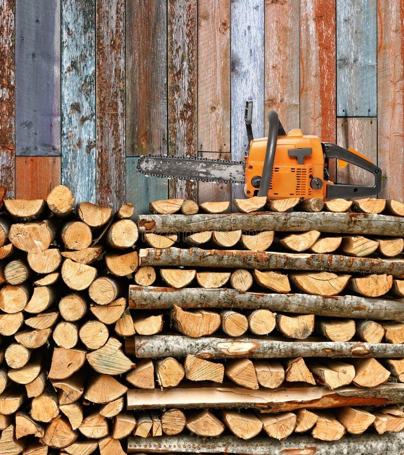 Staplungsbrennholz mit Kettensäge lizenzfreie stockbilder