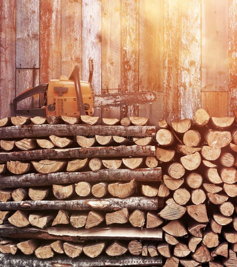 Staplungsbrennholz mit Weinlesekettensäge lizenzfreies stockfoto