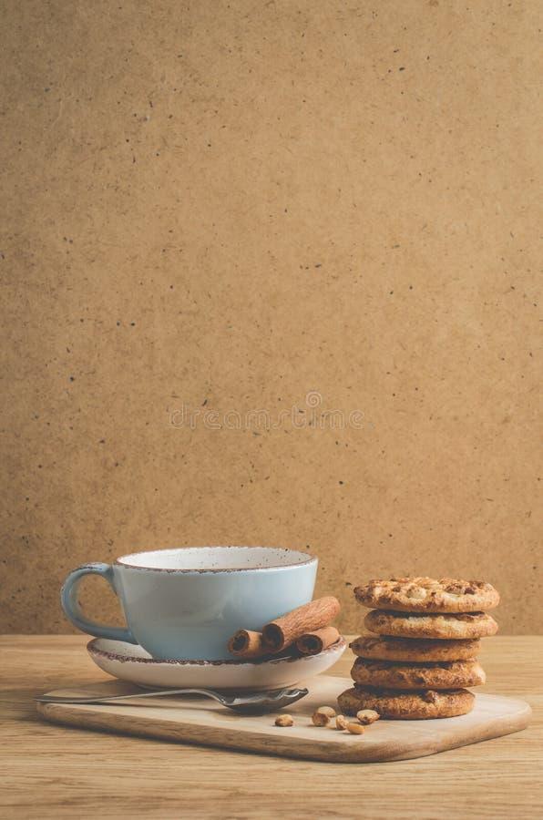 Staplungschipplätzchen mit Nüssen und Kaffeetasse stapelten Chipplätzchen mit Nüssen und Kaffeetasse auf einem hölzernen Hintergr lizenzfreie stockfotografie