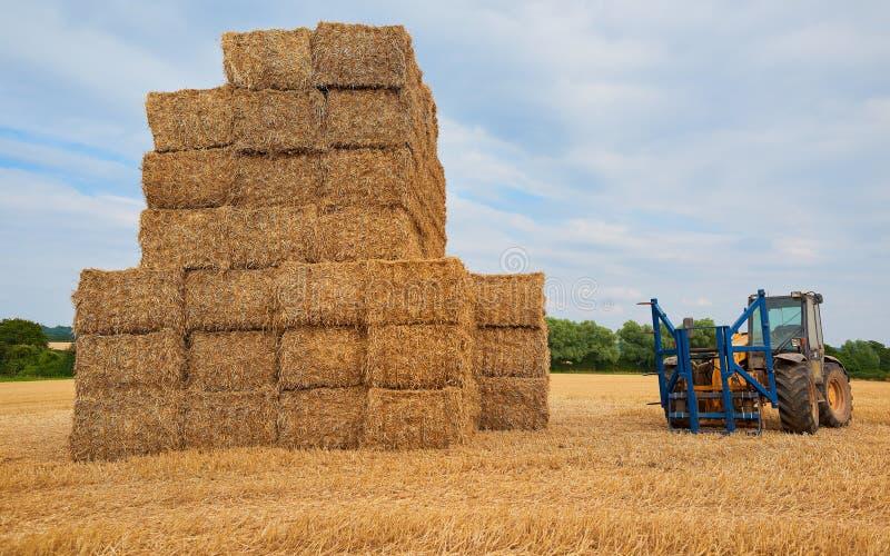 Staplungsheu und ein Traktor lizenzfreie stockfotografie