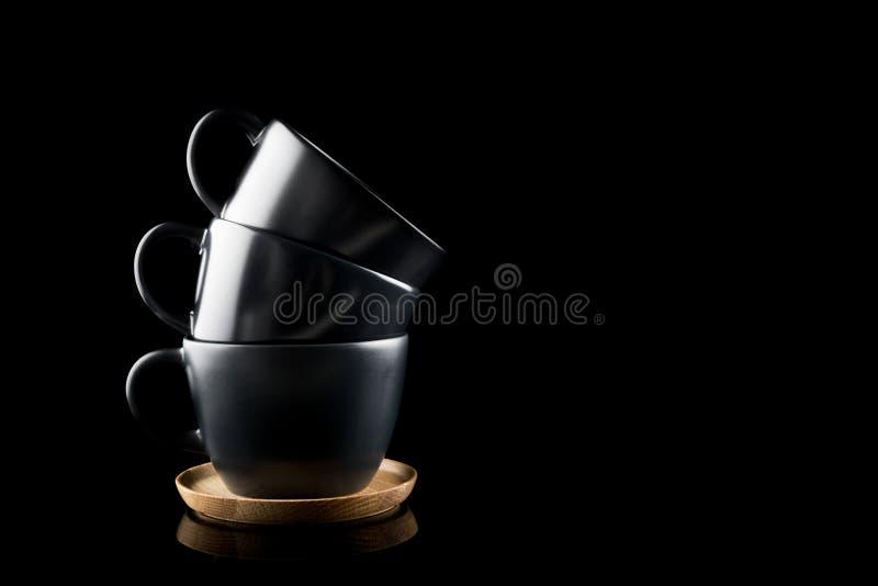 Staplungskaffeetassen, drei dunkle moderne Schalen gestapelt auf einem hölzernen Behälter mit Platz für Ihren Text lizenzfreie stockfotos
