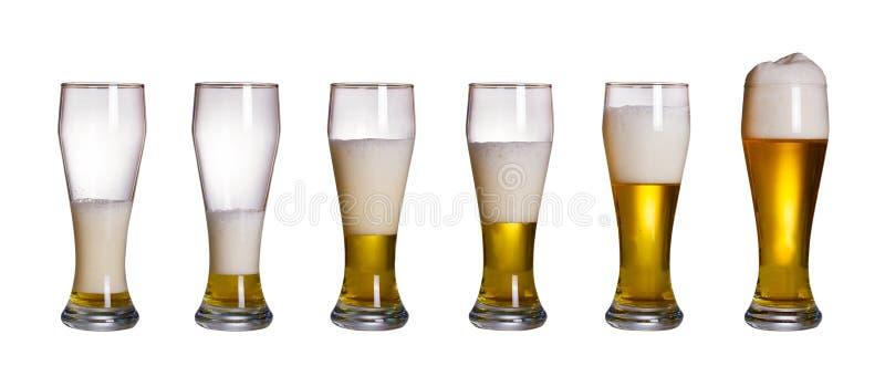 Stappen van het vullen van glas bier, op witte achtergrond worden geïsoleerd die Reeks glazen koud licht bier met schuim stock foto