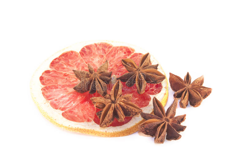 Star anis on a blood grape fuit slice. Brown star anis on a blood, red grape fuit slice royalty free stock image