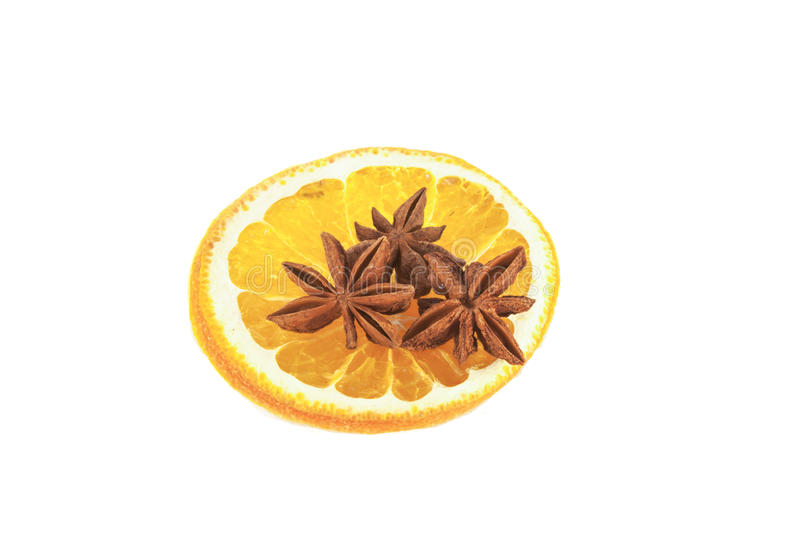 Star anis on a orange. Star anis on a yelloy orange, on isolated white background royalty free stock images
