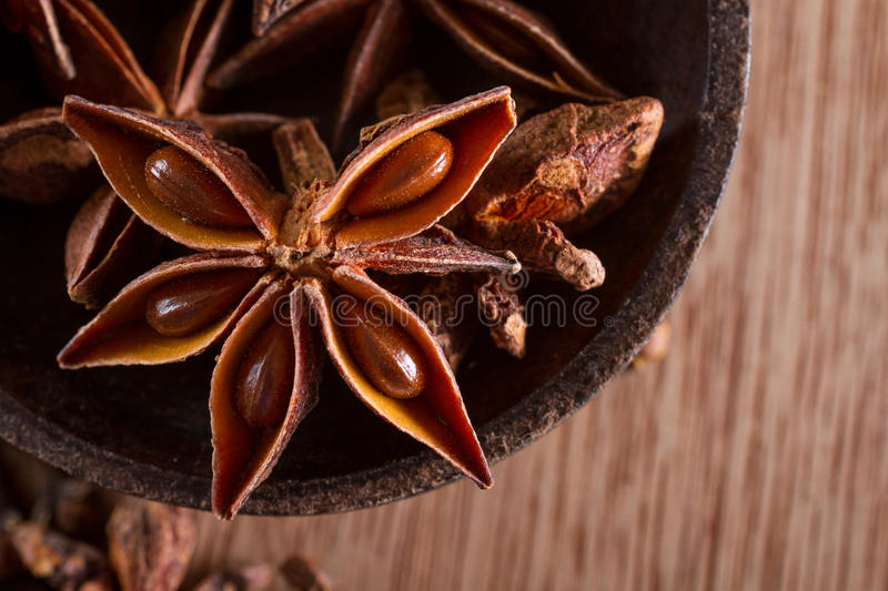 Star anise. Close-up on star anise spice in a bowl, against a wooden background. Macro shot. Copy space stock photo