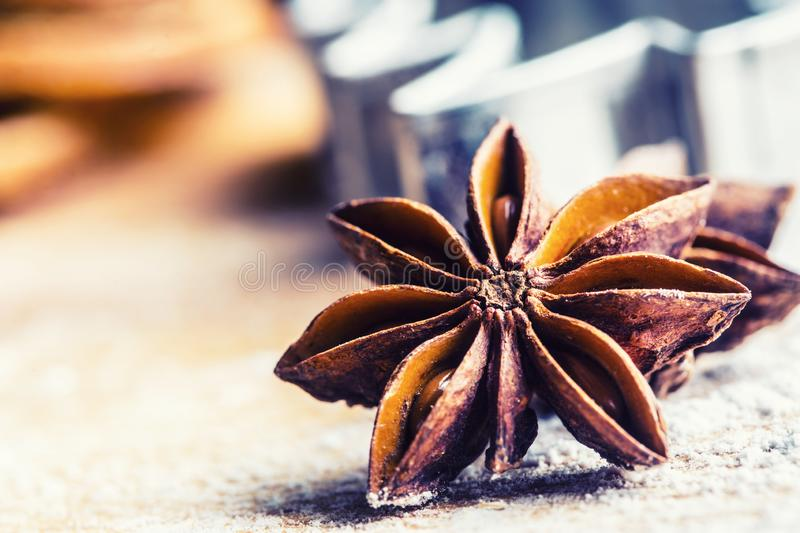 Star anise cookie cutter cinnamon and flour on baking board. Christmas baking utensil and holiday concept stock photo