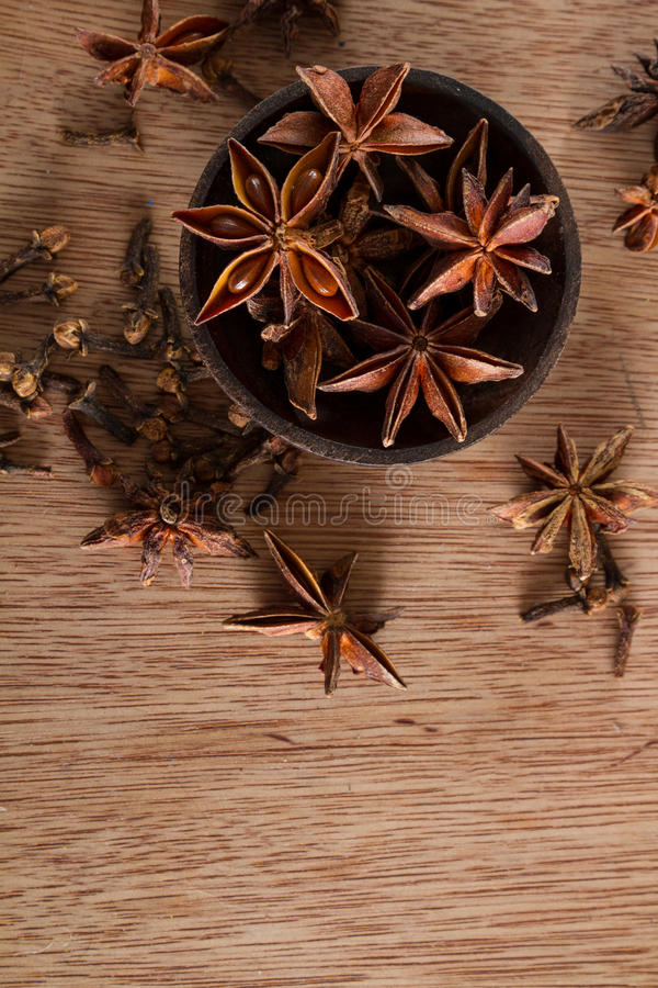 Star anise. Spices for food and decoration, against a rustic wooden background: a bowl full of star anise. Copy space royalty free stock photography