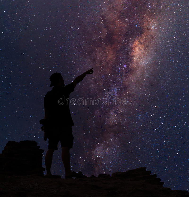 Star-catcher. A person is standing next to the Milky Way galaxy stock images
