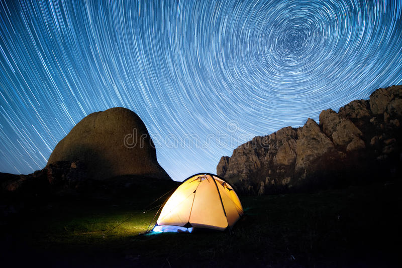 Star circles above the mountains and a glowing camping tent stock photo
