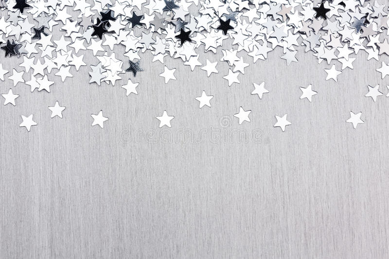 Star confetti on silver metal background royalty free stock photography