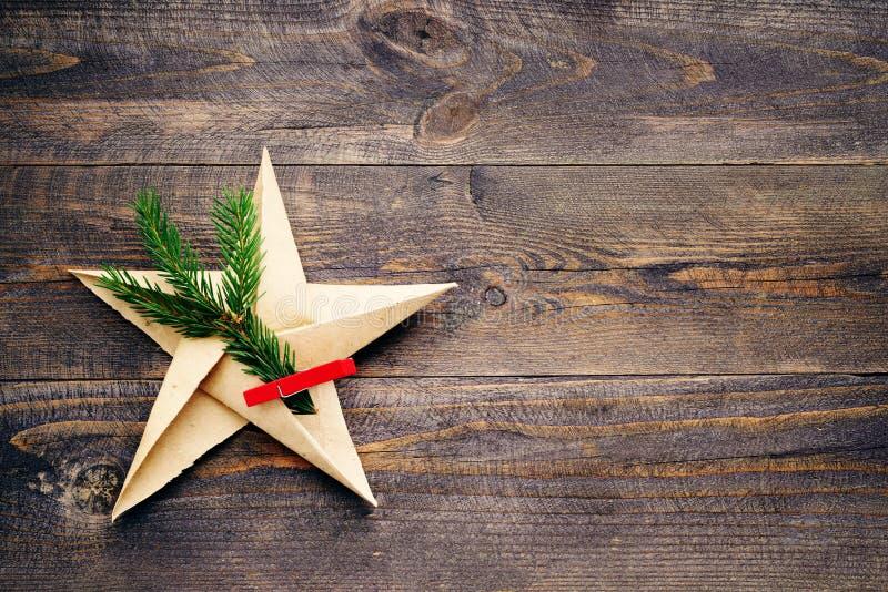 Star do papel e de um ramo do abeto em uma superfície áspera velha de madeira foto de stock royalty free
