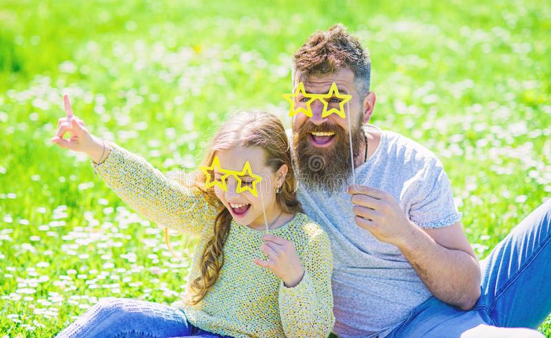 Star and fame concept. Dad and daughter sits on grass at grassplot, green background. Child and father posing with star. Shaped eyeglases photo booth attribute stock photo