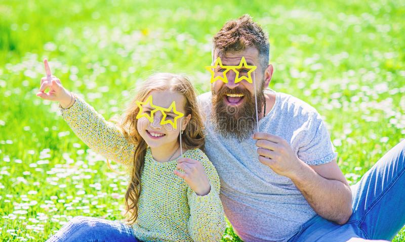 Star and fame concept. Dad and daughter sits on grass at grassplot, green background. Family spend leisure outdoors. Child and father posing with star shaped royalty free stock image