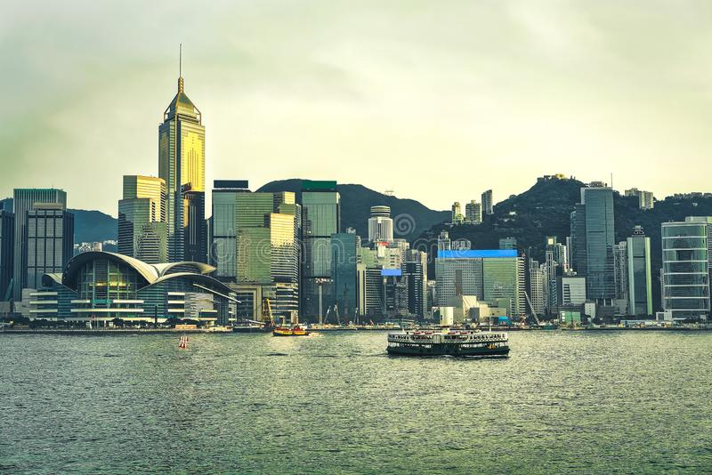 Star ferry at the Victoria Harbour HK at sundown. View from Kowloon on Hong Kong Island stock photography