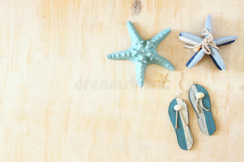 Star fish and wooden flip flops decoration. Star fish and wooden flip flops decoration over white textured wooden background royalty free stock photo