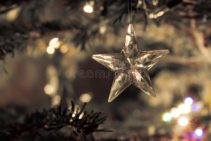 Star of glass with abstract background of holiday lights. And winter background on yellow for festive occasions stock image