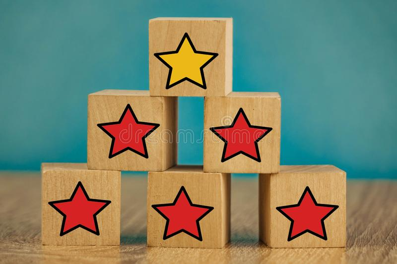 Star icon yellow and red on wooden cubes far from blue background. Five, sense, best, business, customer, evaluation, excellent, feedback, goal, good stock photos