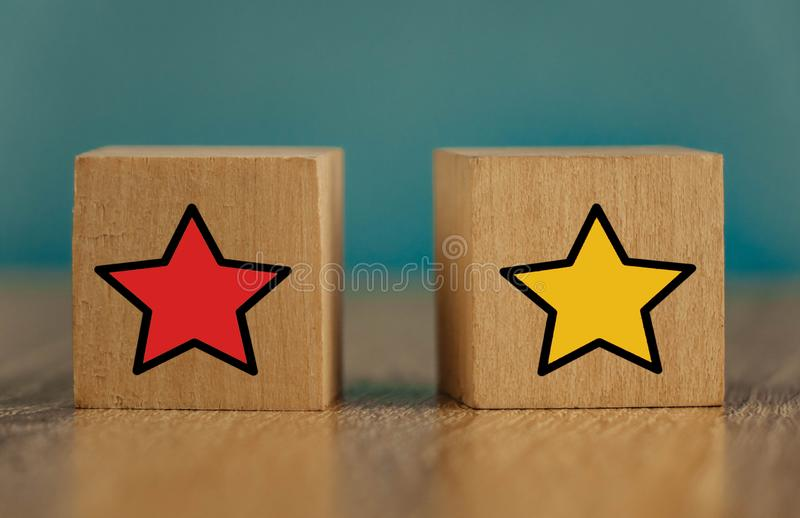 Star icon yellow and red on wooden cubes far from blue background. Five, sense, best, business, customer, evaluation, excellent, feedback, goal, good stock images