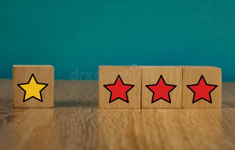 Star icon yellow and red on wooden cubes far from blue background. Five, sense, best, business, customer, evaluation, excellent, feedback, goal, good royalty free stock photo