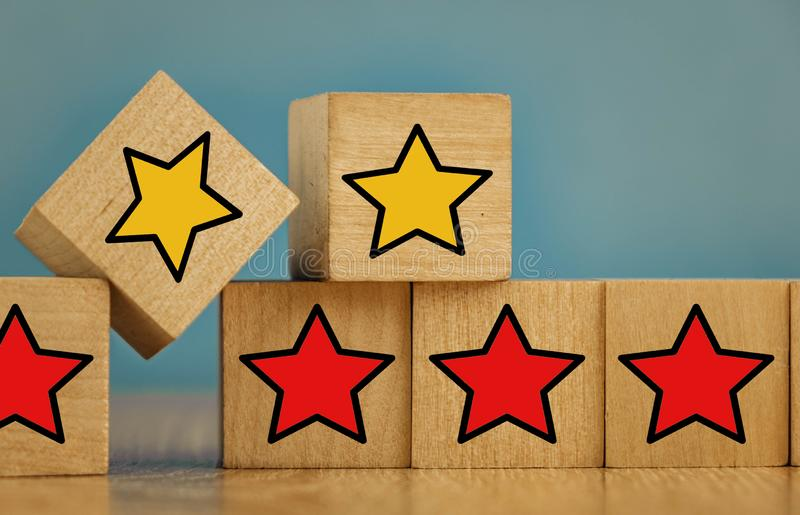 Star icon yellow and red on wooden cubes far from blue background. Five, sense, best, business, customer, evaluation, excellent, feedback, goal, good royalty free stock photos