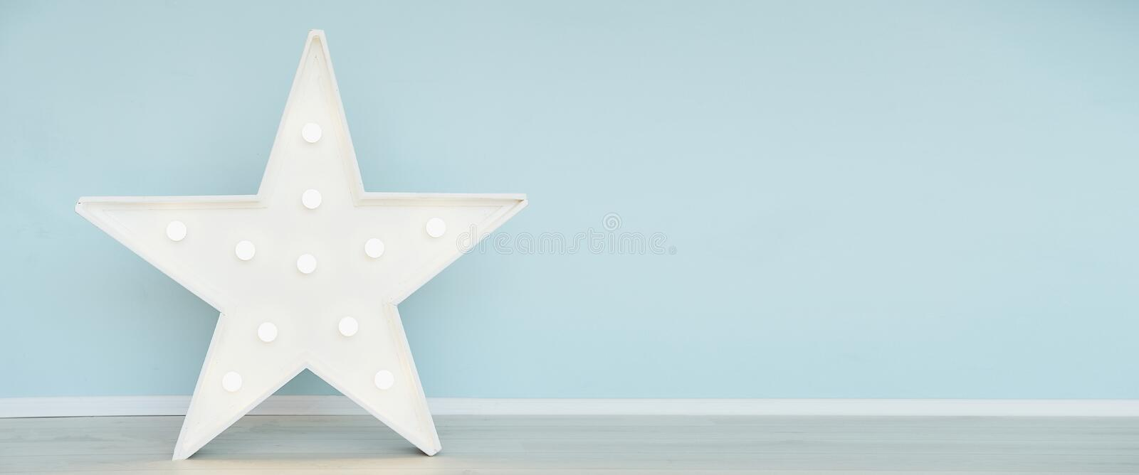 Star lamp on floor on background of blue wall. Big star with bulb lights. Modern home decoration royalty free stock photos