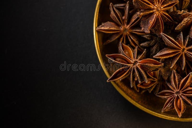Star shape anis seeds in bowl on black slate stock photo