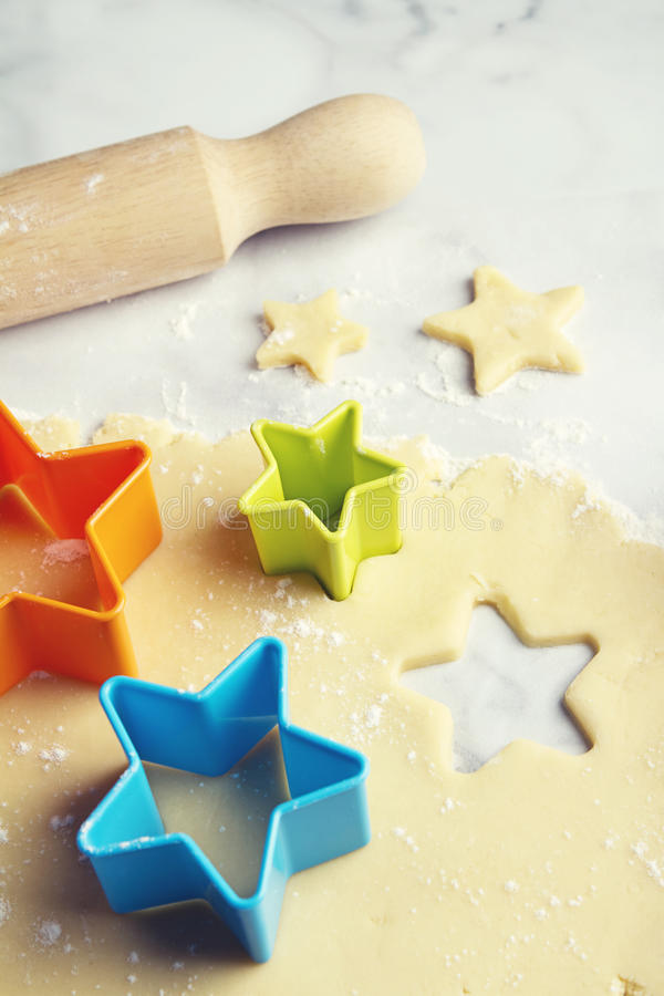 Star shape cookie cutter in dough vertical stock photo