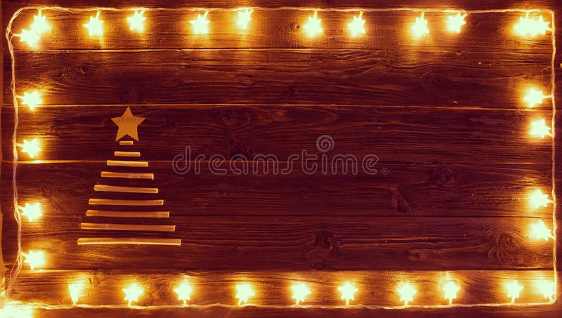 Star shaped Christmas lights and christmas tree from dry wooden sticks on brown wooden background with copy space.  royalty free illustration