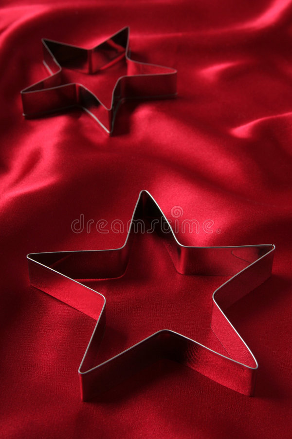 Star Shaped Cookie Cutters. On a Red Satin royalty free illustration