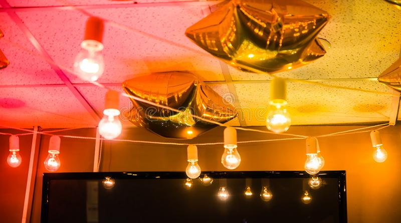 Star shaped golden balloons under the ceiling with a garland of light bulbs royalty free stock photo