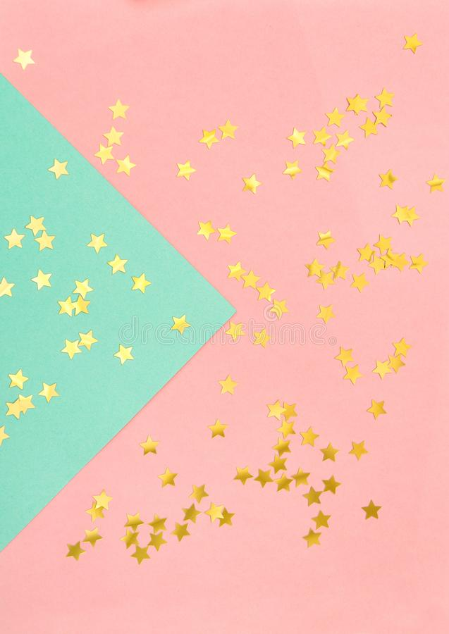 Star shaped golden confetti pink blue flat lay background stock photos