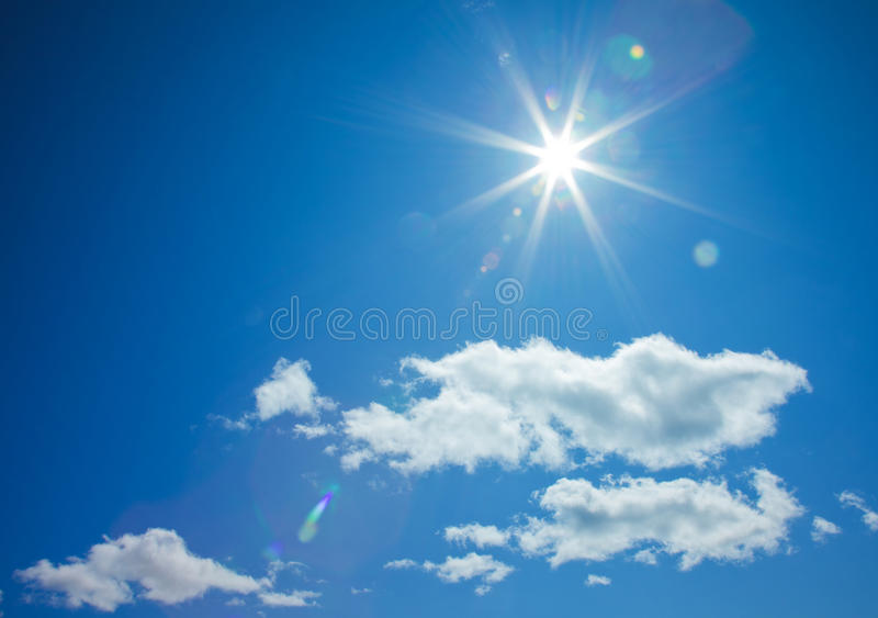 Star-shaped sun in blue sky. With light clouds royalty free stock images