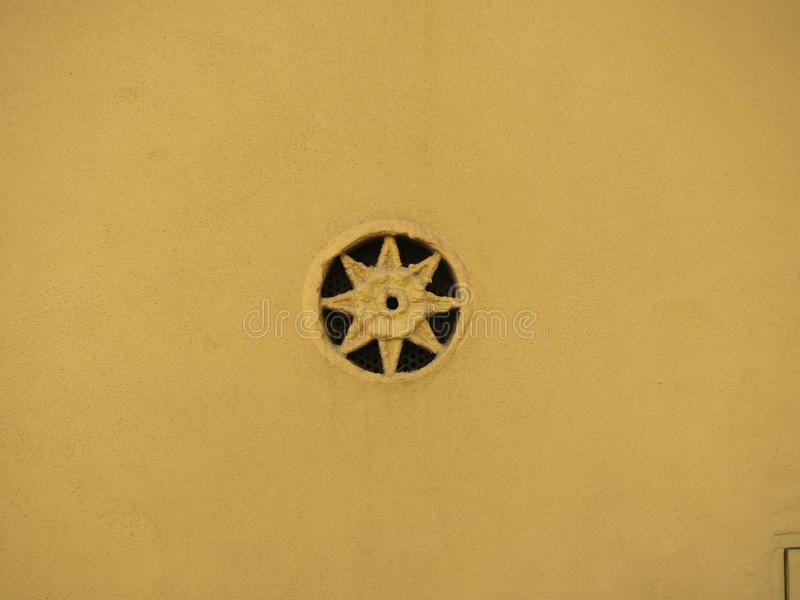 Star shaped ventilation hole in an ochre colored stone wall stock images