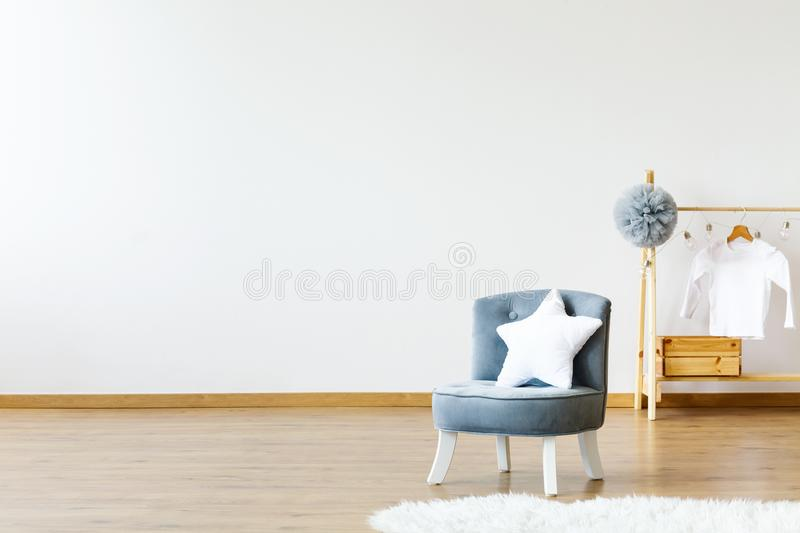 Star shaped white pillow placed on small armchair standing in white baby room interior with grey pompom and white shirt on wooden royalty free stock image