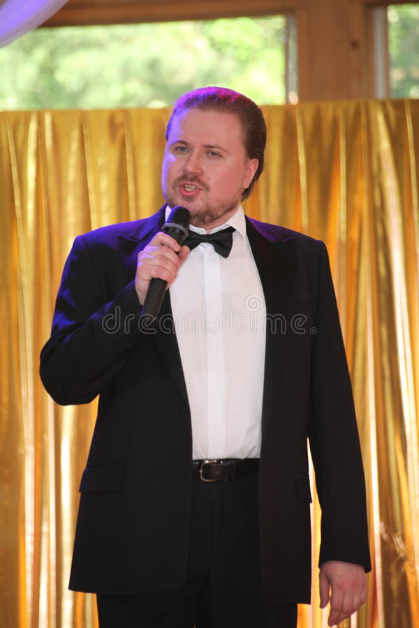 Star of stage, Opera singer, tenor Sergey Muravyov acts, sings in the black concert tuxedo coat. At the presentation of the menu of Ukrainian national cuisine stock photo