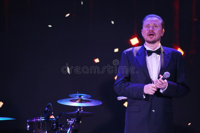 Star of stage, Opera singer, tenor Sergey Muravyov acts, sings the formal tuxedo costume. On the stage of a nightclub Olympia, Saint Petersburg, Russia, Europe stock image
