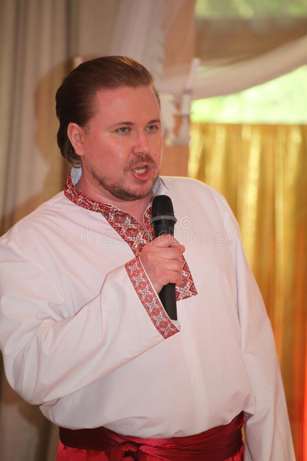 Star of stage, Opera singer, tenor Sergey Muravyov acts, sings the national Ukrainian Russian costume. At the presentation of the menu of Ukrainian national royalty free stock image
