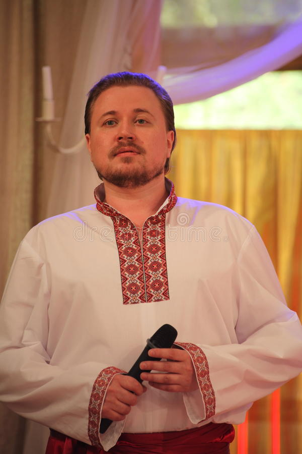 Star of stage, Opera singer, tenor Sergey Muravyov acts, sings the national Ukrainian Russian costume. At the presentation of the menu of Ukrainian national stock photo