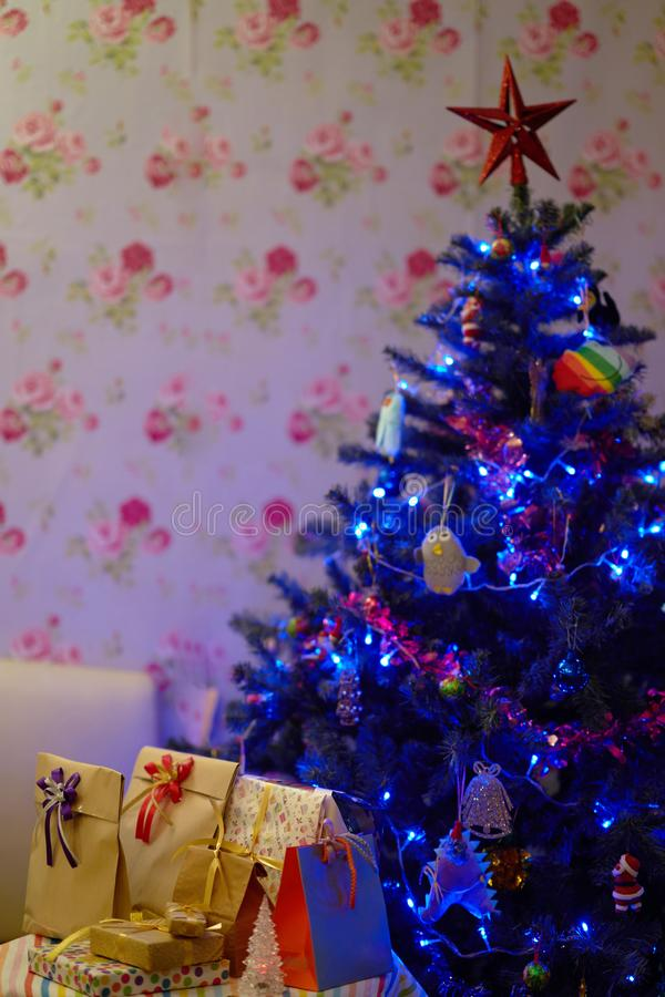 Star on top decorated Christmas tree with present boxes inside house.  stock photography