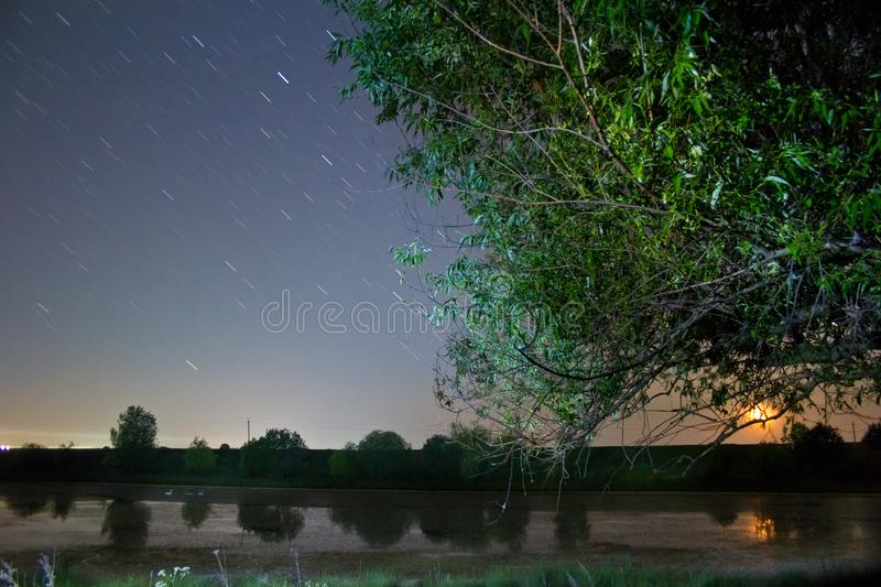 Star tracks in clear deep blue night sky, beautiful countryside landscape with a small lake, willow and rising moon. Star tracks in clear deep blue night sky royalty free stock photos